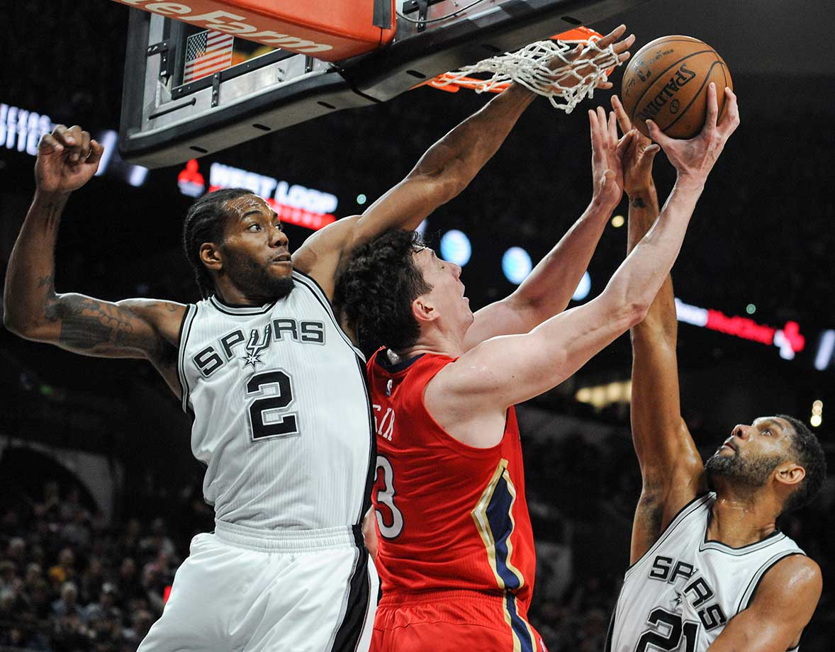 San Antonio forwards Kawhi Leonard, left, and Tim Duncan defend New Orleans center Omer Asik.