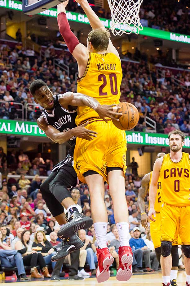 Thaddeus Young of the Brooklyn Nets passes around Timofey Mozgov of the Cleveland Cavaliers.