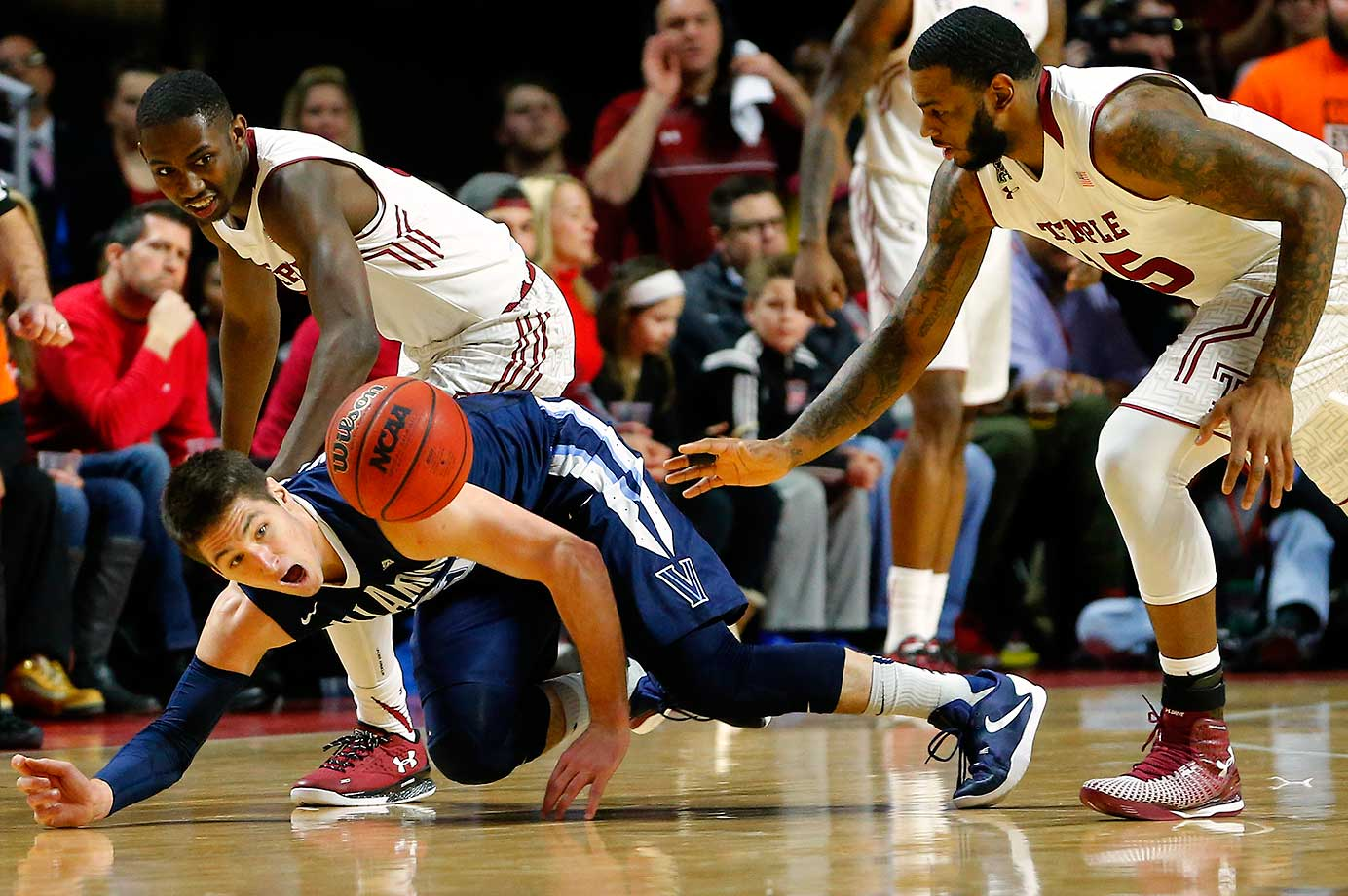 Ryan Arcidiacono of Villanova attempts to regain possession of the ball as Temple's Levan Shawn Alston, Jr. (No. 3) and Jaylen Bond defend.