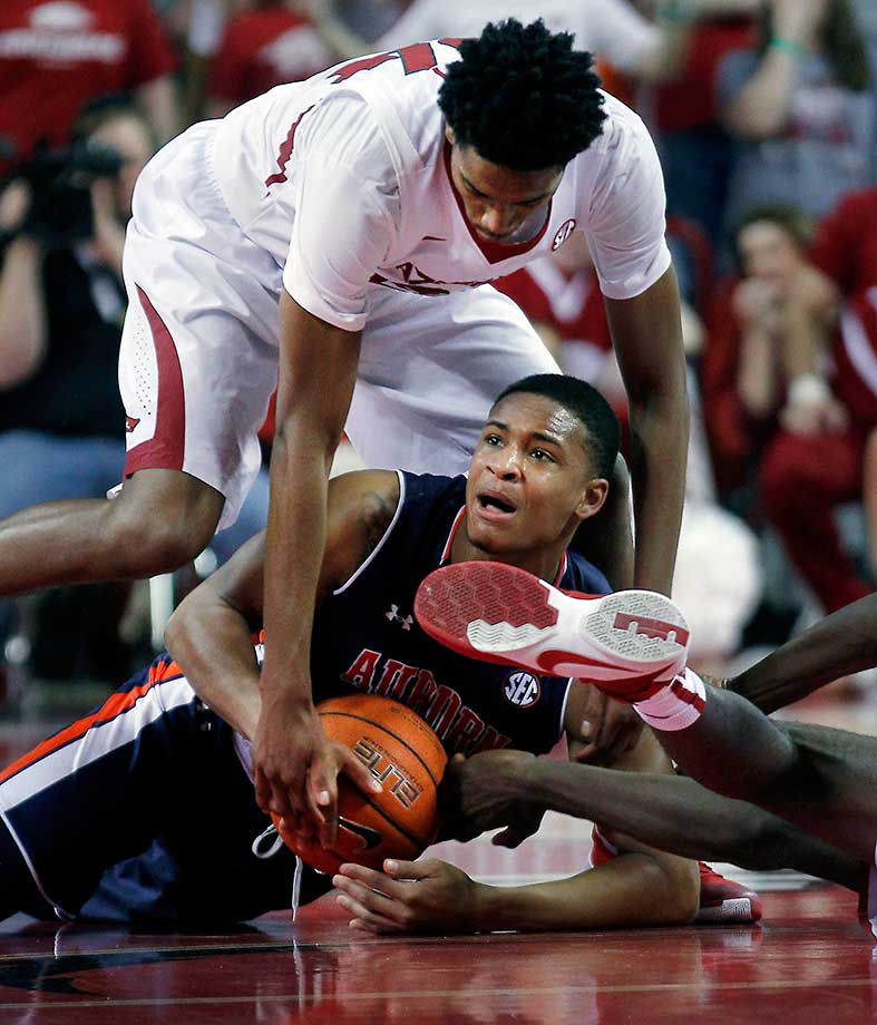 Auburn's Bryce Brown keeps the ball underneath him as Arkansas' Jimmy Whitt tumbles over.