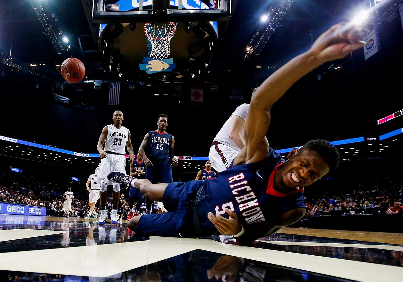 Trey Davis of the Richmond Spiders is fouled by Jashire Hardnett of the Fordham Rams.