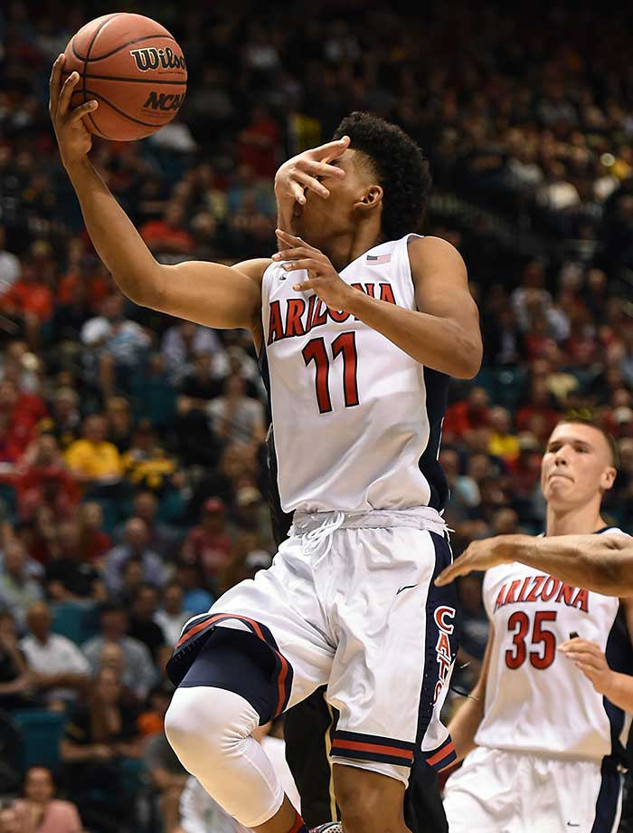 Allonzo Trier of Arizona is hit in the face as he drives to the basket against Colorado.