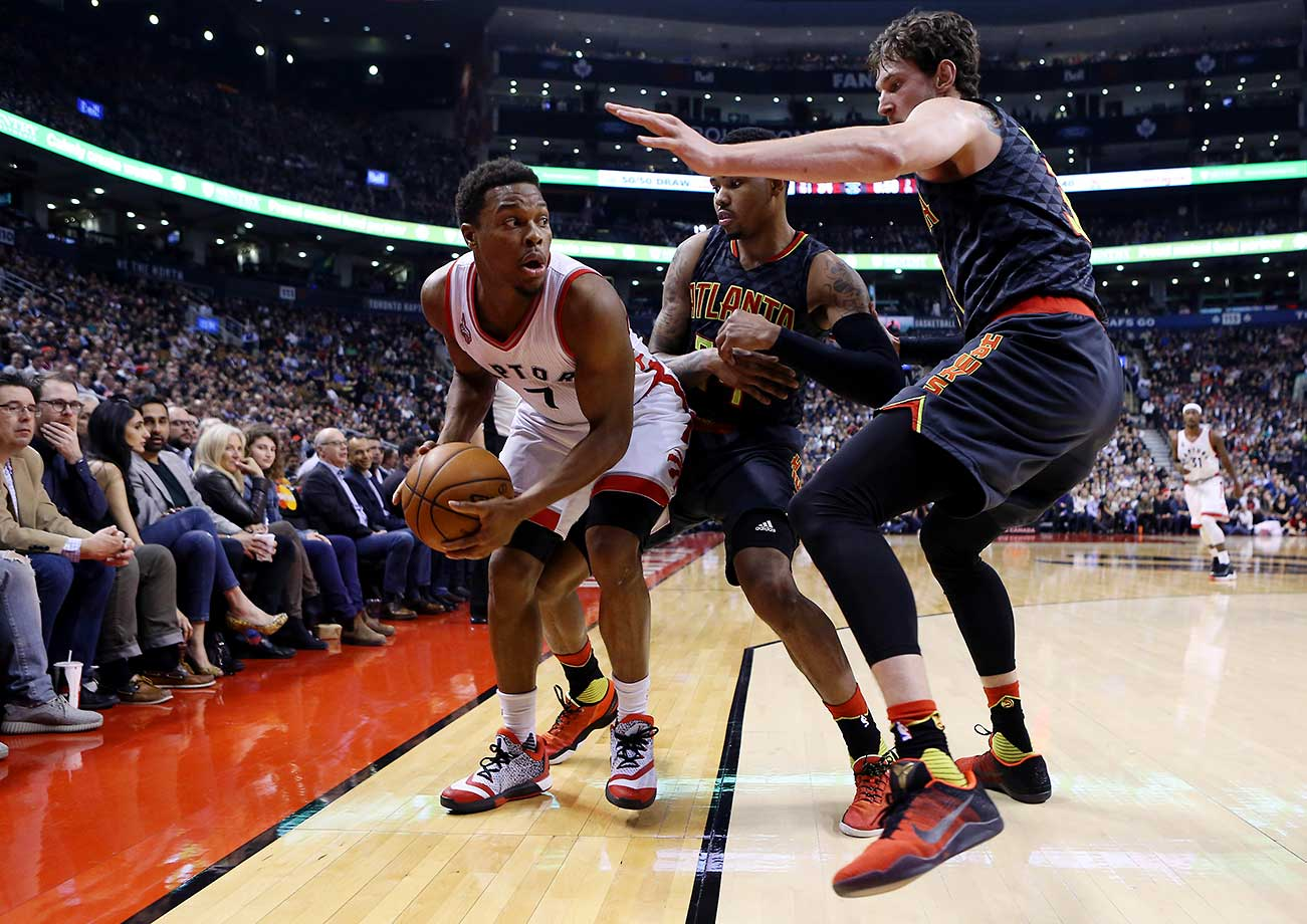 Kyle Lowry of Toronto is trapped by Kent Bazemore and Mike Muscala of the Atlanta Hawks.
