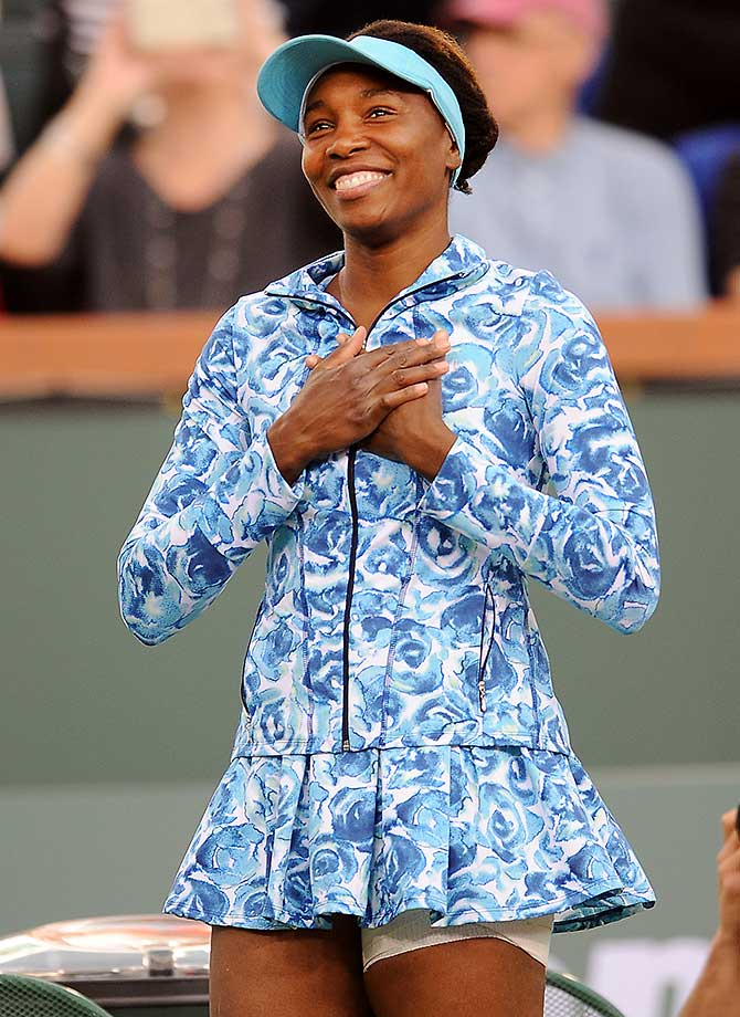 Playing in her first match in Indian Wells since 2001, Venus Williams responds to the cheering fans.