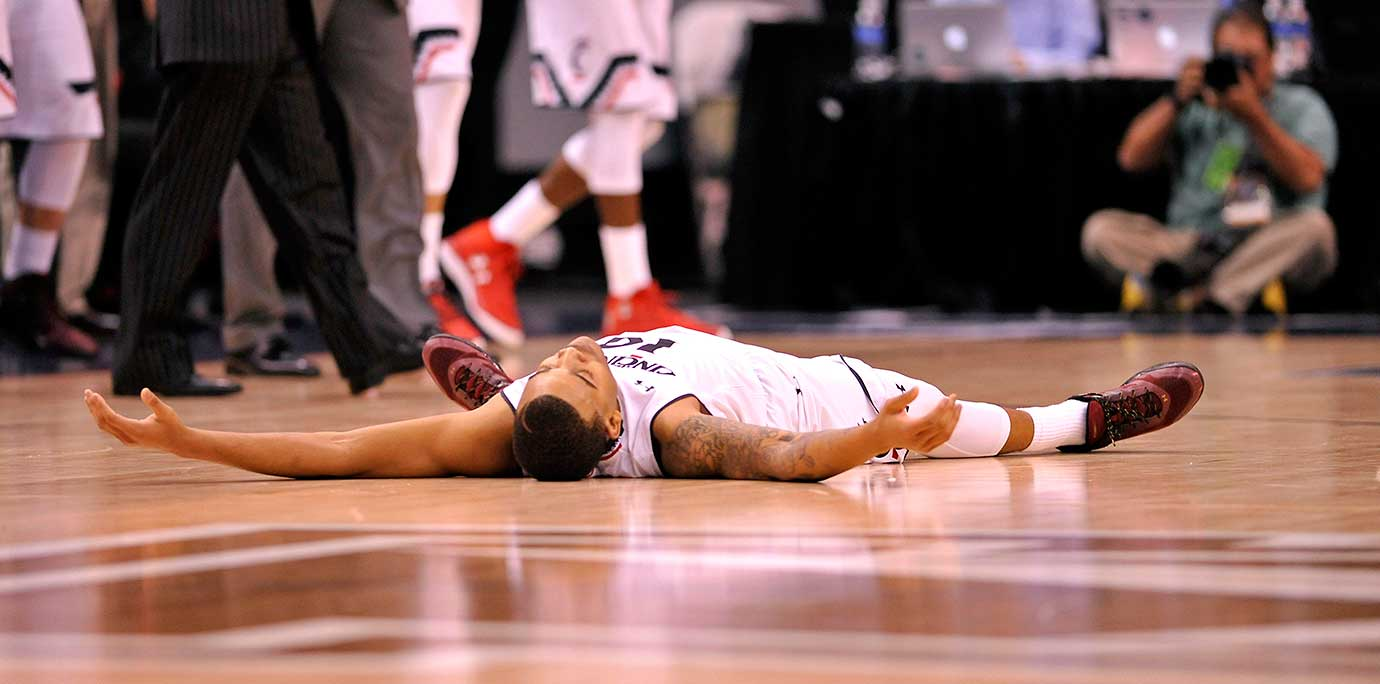 Cincinnati's Troy Caupain exhausted after the first of four overtime periods against Connecticut.
