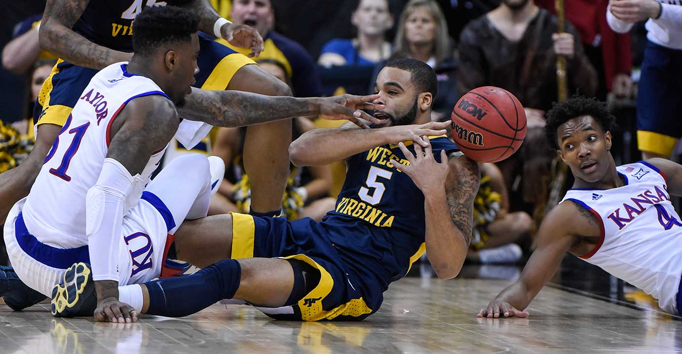 Jaysean Paige of West Virginia tries to gain control of a loose ball against Jamari Traylor (31) and Devonte' Graham of Kansas.