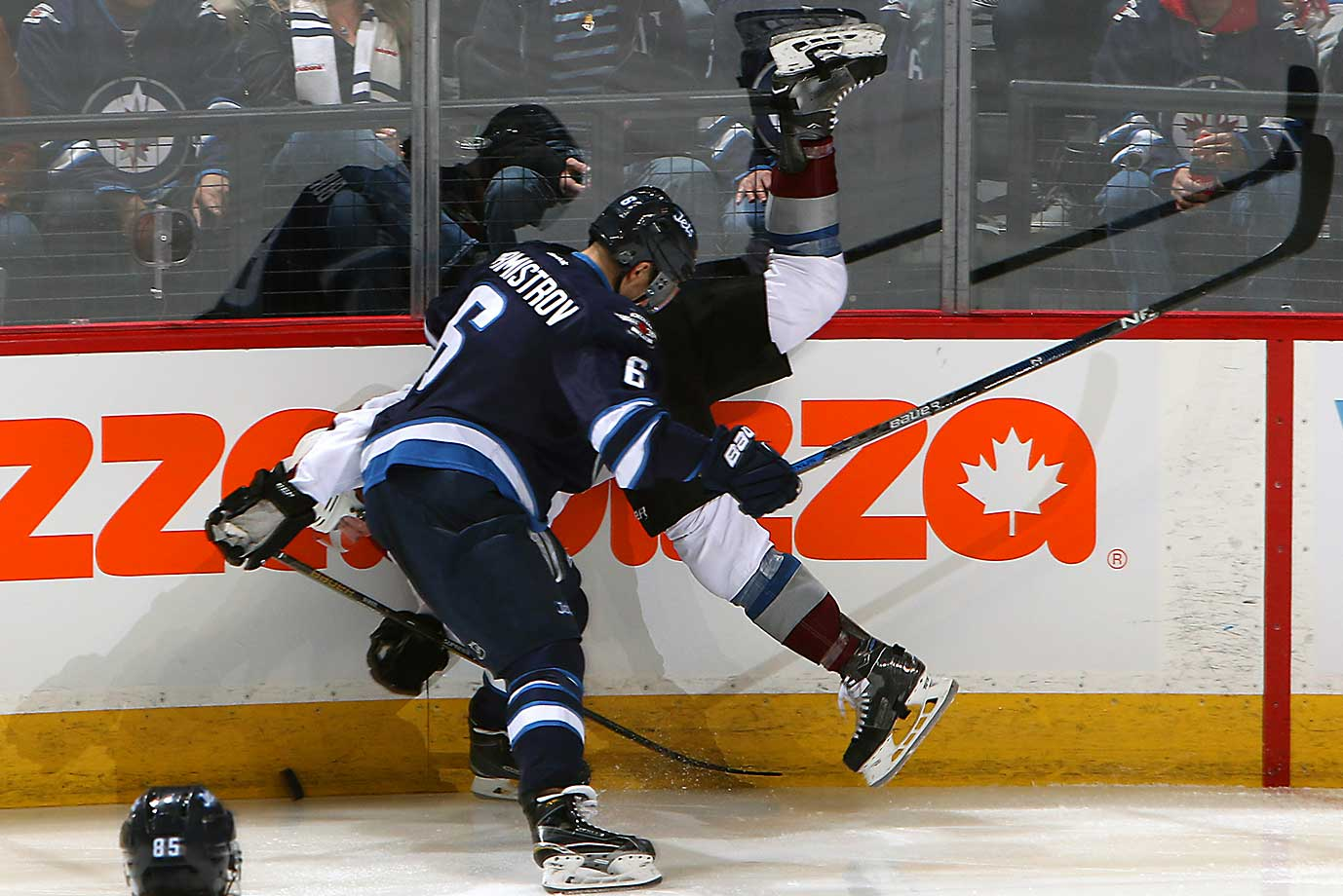 Alexander Burmistrov of Winnipeg checks Tyson Barrie of the Colorado Avalanche.