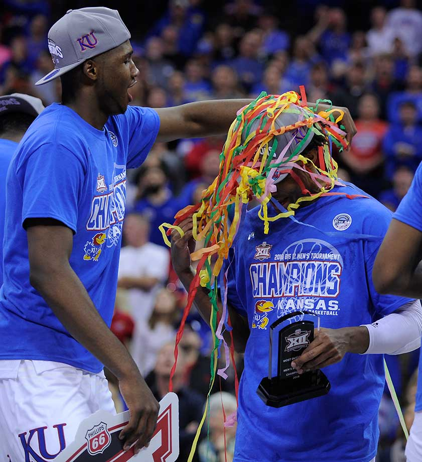Carlton Bragg Jr. of the Kansas Jayhawks wraps confetti around Devonte' Graham as they celebrate winning the Big 12.