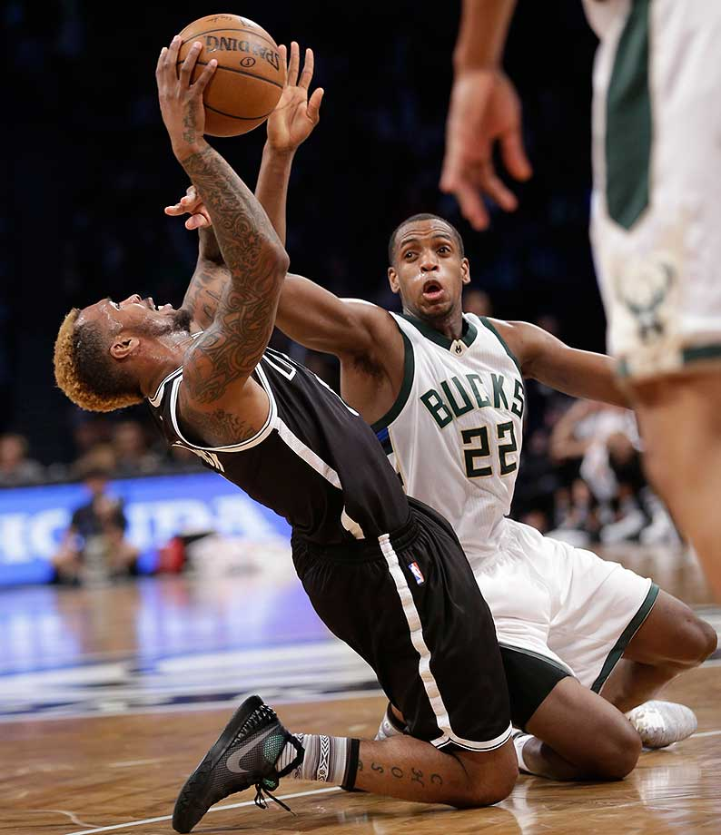 Sean Kilpatrick of Brooklyn tries to keep control of the ball while Milwaukee's Khris Middleton defends.