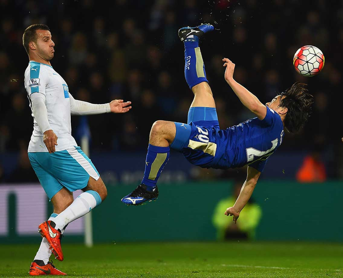 Shinji Okazaki of Leicester City scores with an overhead kick as Steven Taylor of Newcastle United looks on.