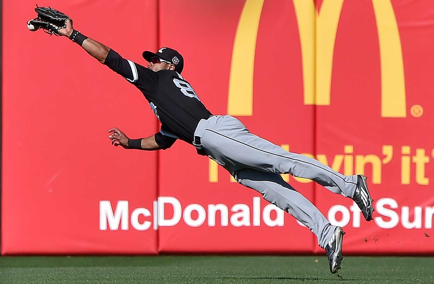 Chicago White Sox center fielder Jacob May deflects an RBI double hit by Omar Infante of Kansas City.