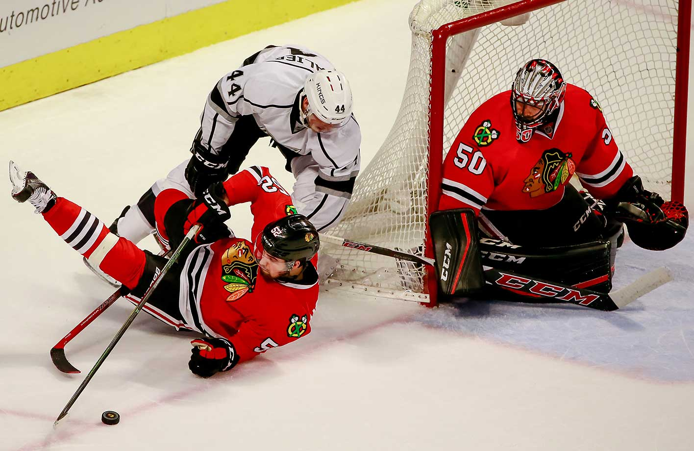 Erik Gustafsson of the Chicago Blackhawks is hit by Vincent Lecavalier of the Los Angeles Kings next to goalie Corey Crawford.