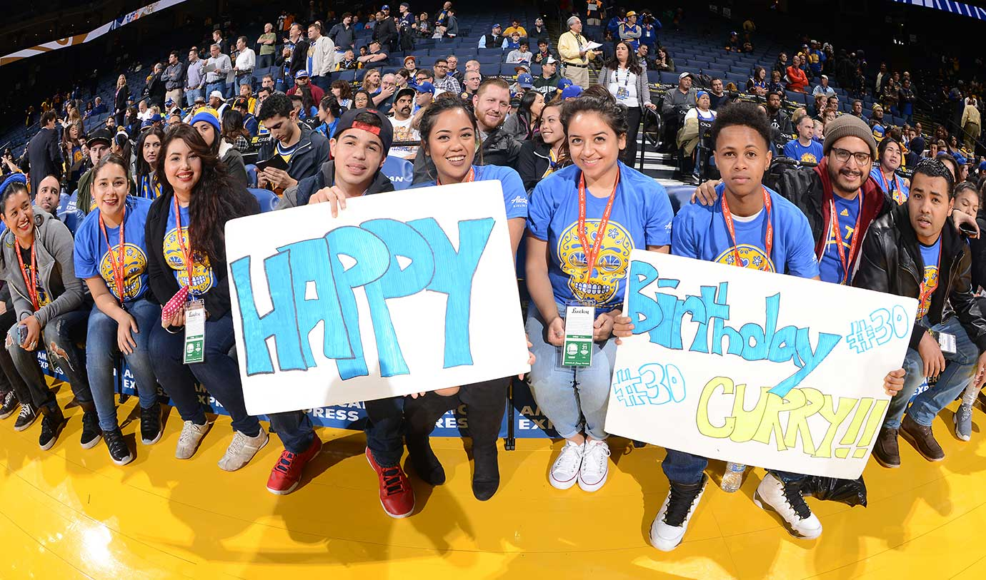 Fans hold up a happy birthday sign for Stephen Curry of the Golden State Warriors on his 28th birthday.