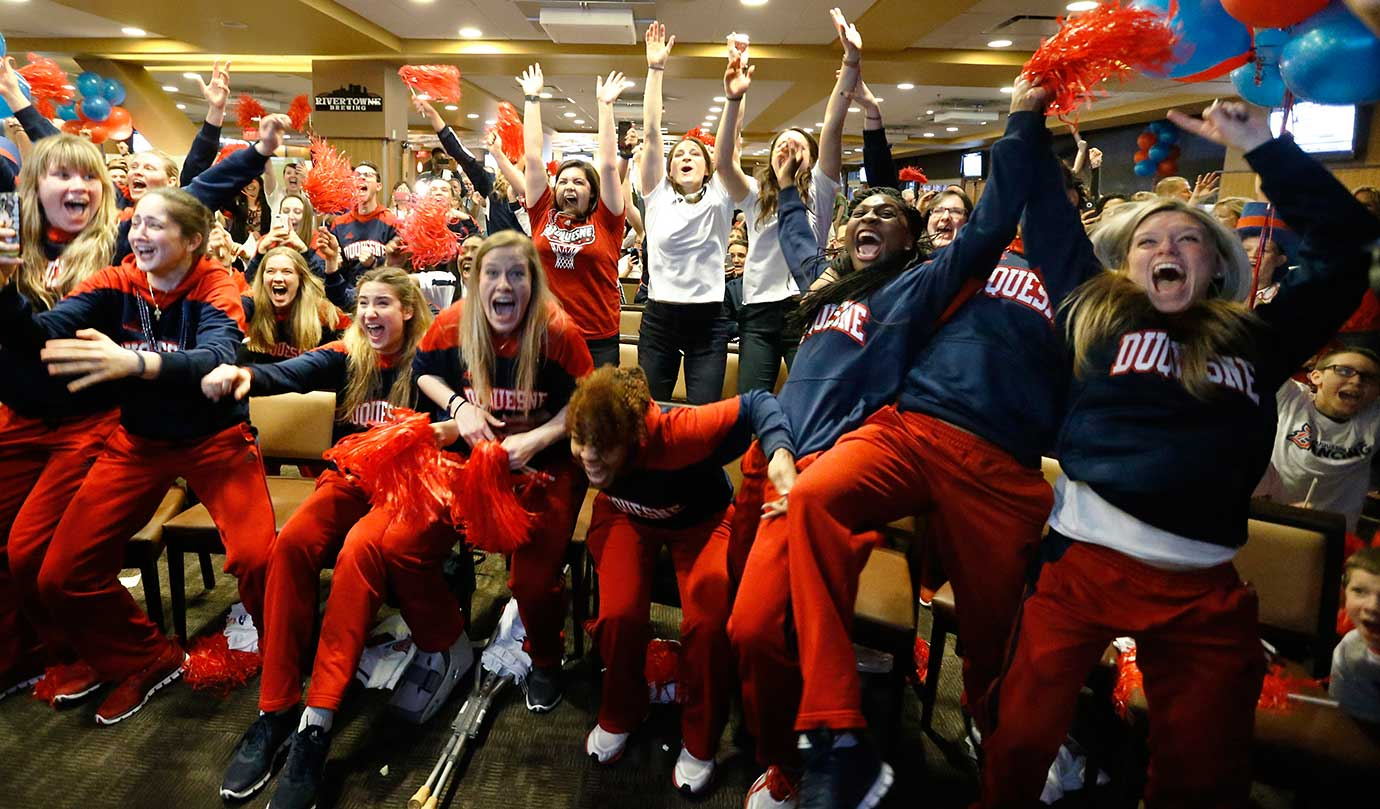 The Duquesne basketball team celebrates as it hears of the school's first-ever berth in the NCAA women's college basketball tournament.