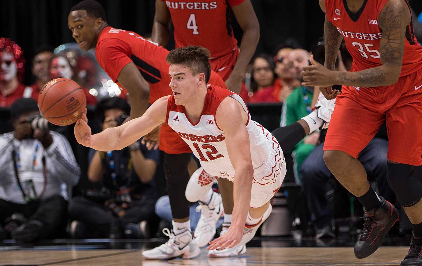 Nebraska forward Michael Jacobson taps a loose ball to a teammate while facing Rutgers.
