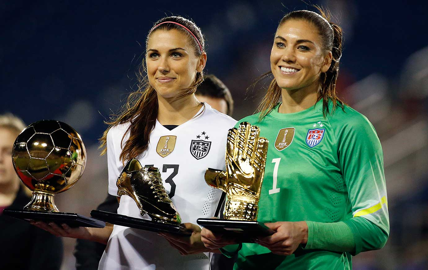 Alex Morgan, left, and Hope Solo pose with their trophies after winning the SheBelieves Cup tournament.