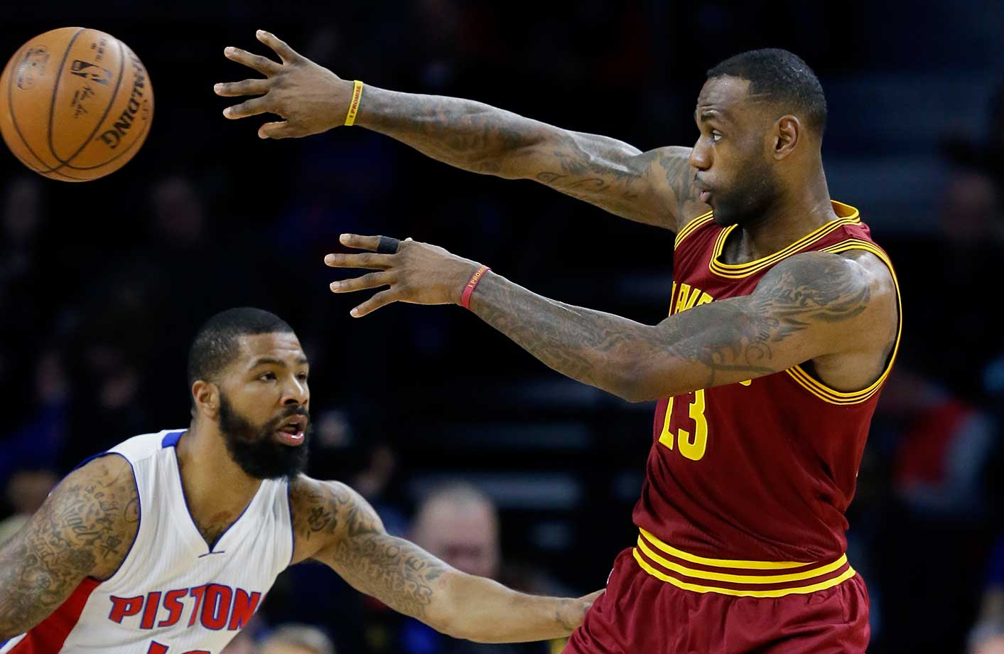LeBron James passes in front of Detroit Pistons forward Marcus Morris in Auburn Hills, Mich.