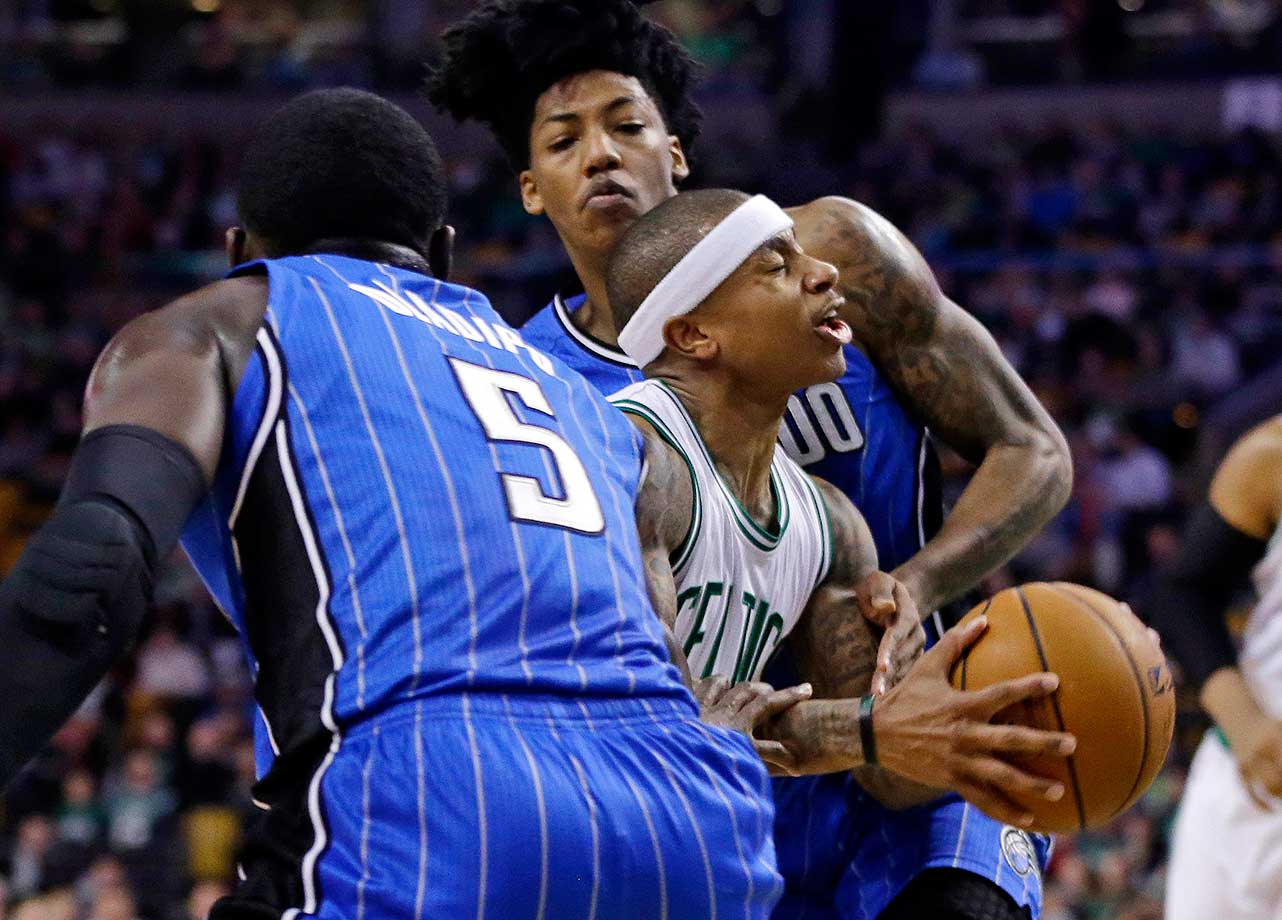 Boston Celtics guard Isaiah Thomas drives through the defense of Orlando Magic guards Victor Oladipo (5) and Elfrid Payton in Boston.