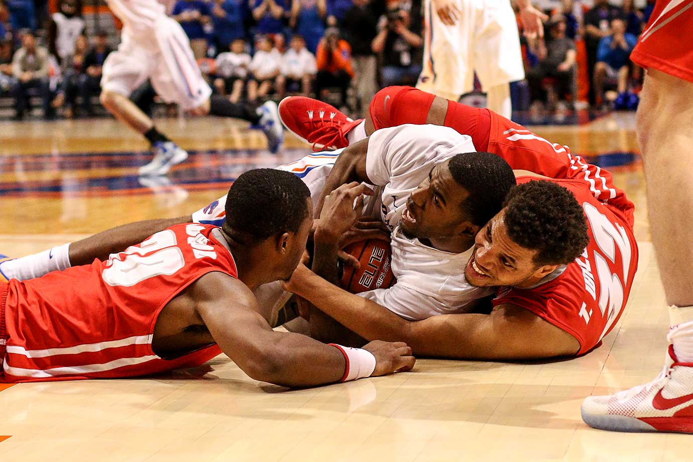 Mikey Thompson of the Boise State Broncos and Tim Williams of the New Mexico Lobos grapple for a loose ball at Taco Bell Arena in Boise, Idaho. New Mexico won 88-83.