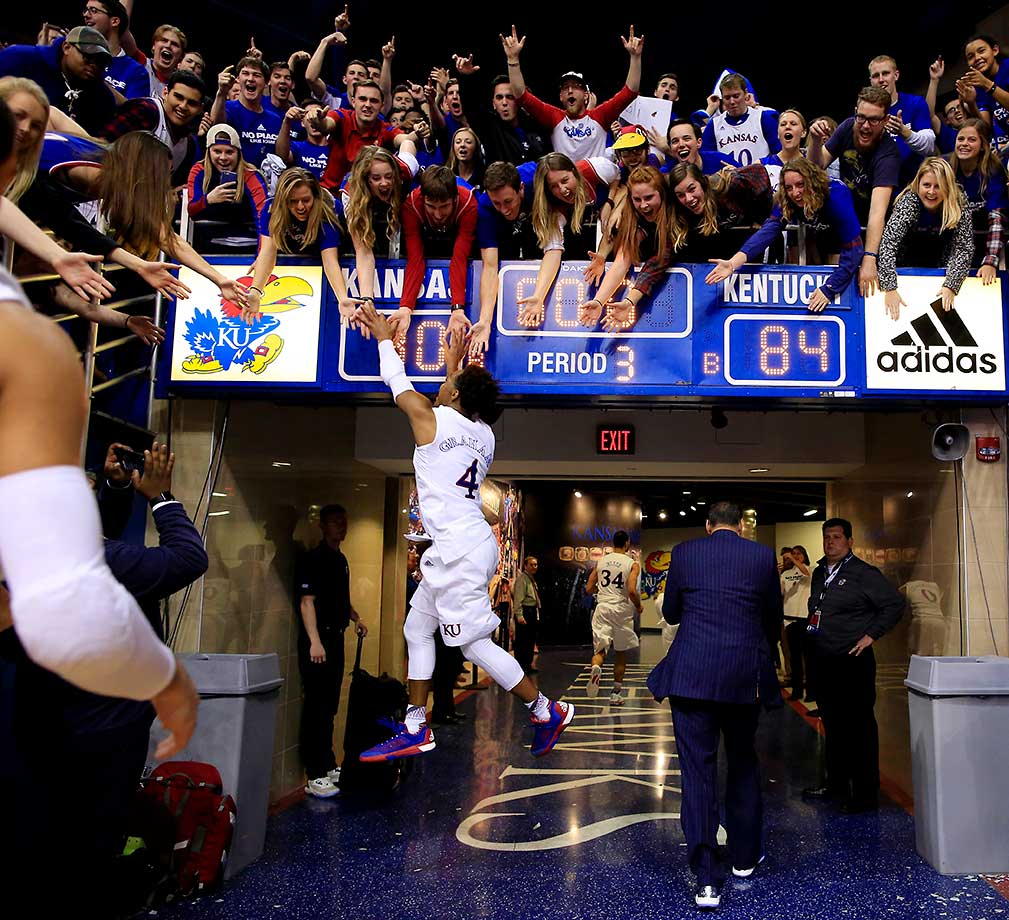 Devonte' Graham of the Kansas Jayhawks leaps to high-five fans as he runs off the floor following the Jayhawks 90-84 overtime victory over the Kentucky Wildcats to win the game at Allen Fieldhouse oin Lawrence, Kansas.