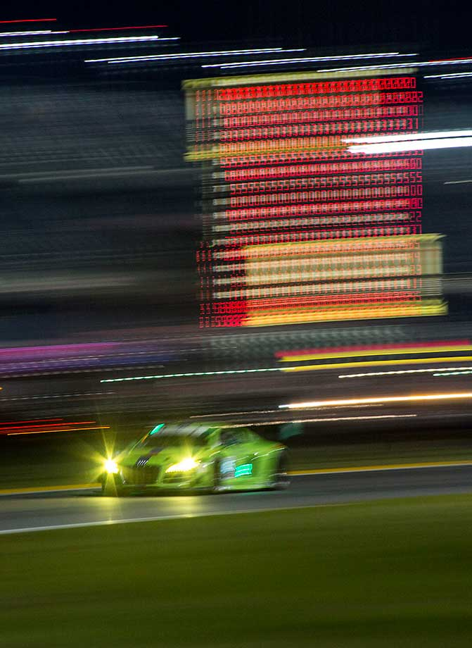 A races car drives past a scoring tower at night during the Rolex 24 at Daytona at Daytona International Speedway in Daytona Beach, Fla.