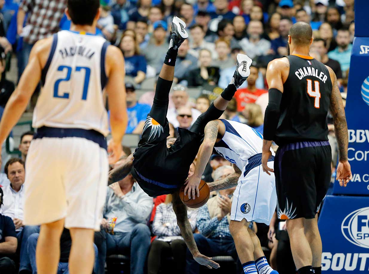 Zaza Pachulia and Tyson Chandler watch as Archie Goodwin flips over Dallas Mavericks' Deron Williams. Goodwin was defending as Williams was attempting a shot.