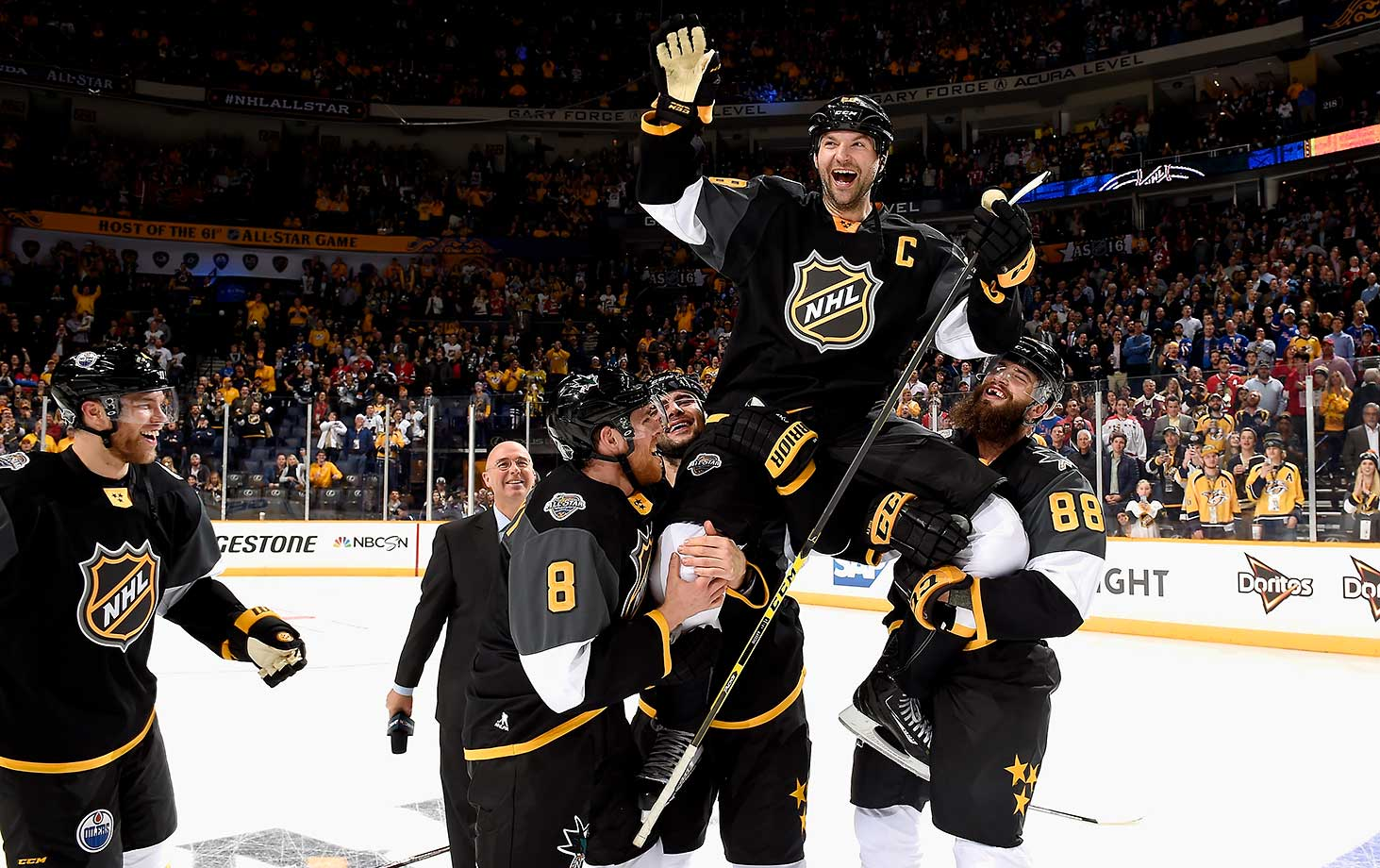 John Scott of the Arizona Coyotes is held up by teammates Mark Giordano of the Calgary Flames and Brent Burns and Joe Pavelski of the San Jose Sharks of the Pacific Division All-Stars after defeating the Atlantic Division All-Stars 1-0 in the 2016 Honda NHL All-Star Final Game at Bridgestone Arena in Nashville.