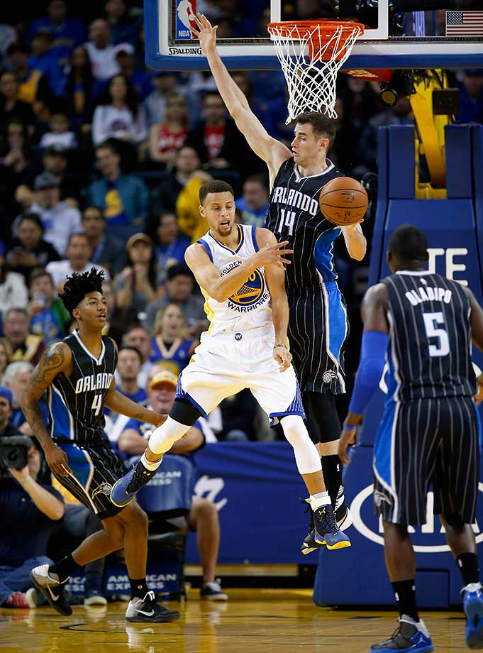 Stephen Curry of Golden State passes around Jason Smith of Orlando on a night when the Warriors won their 45th straight at home.