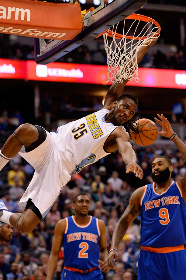 Denver forward Kenneth Faried hangs on to the rim after a big dunk against the Knicks.