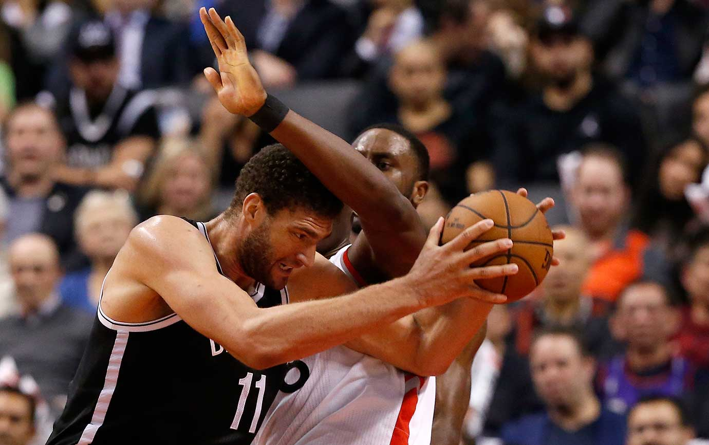 Toronto Raptors center Bismack Biyombo fouls Brooklyn center Brook Lopez.