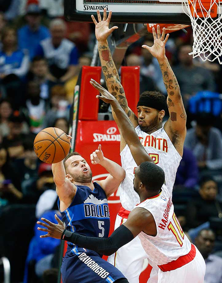 Dallas Mavericks guard J.J. Barea passes as he defended by Hawks forward Mike Scott (32) and guard Dennis Schroder in Atlanta.