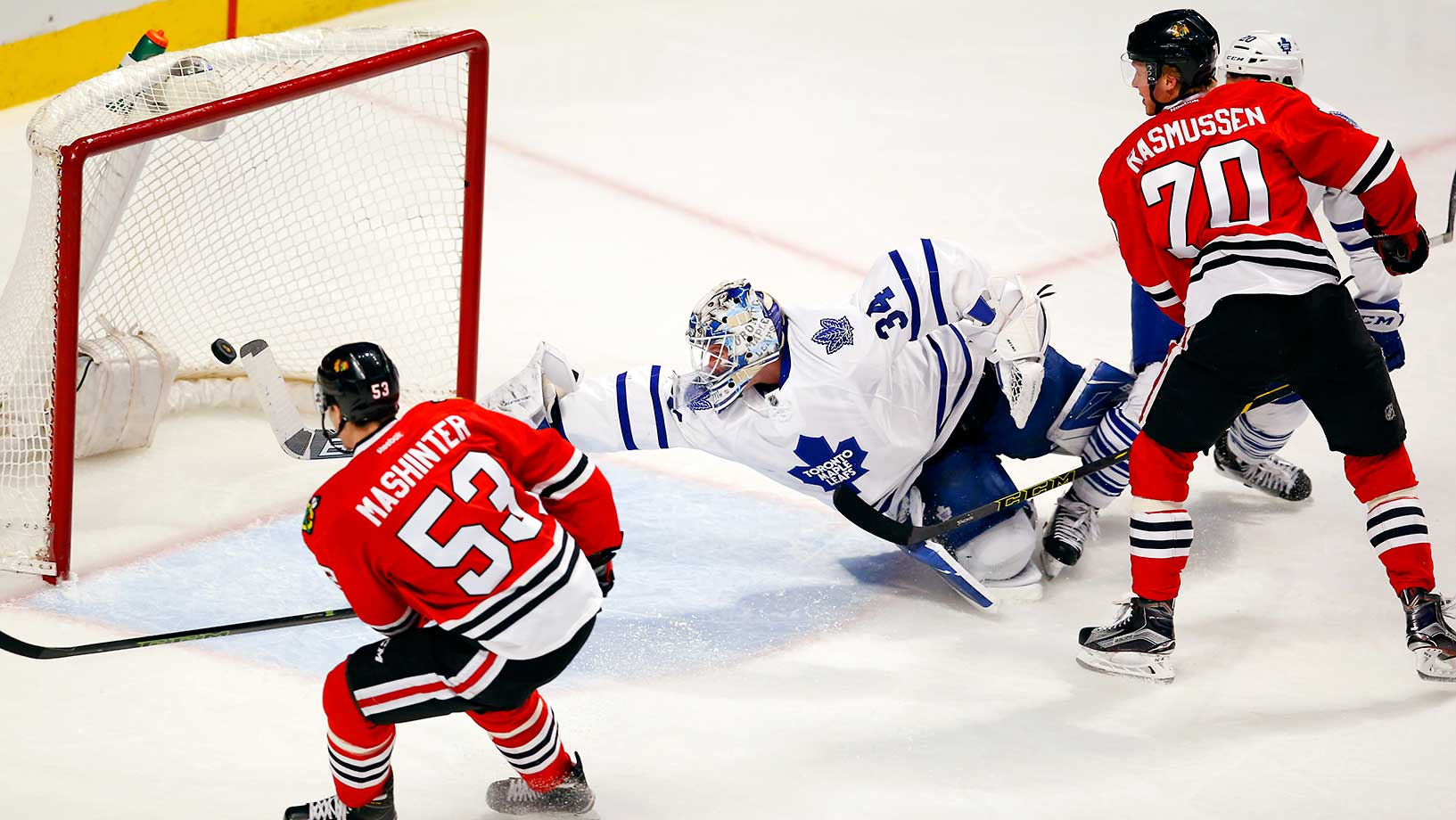 Toronto goalie James Reimer dives to make a save as Brandon Mashinter (53) and Dennis Rasmussen of the Chicago Blackhawks look on.