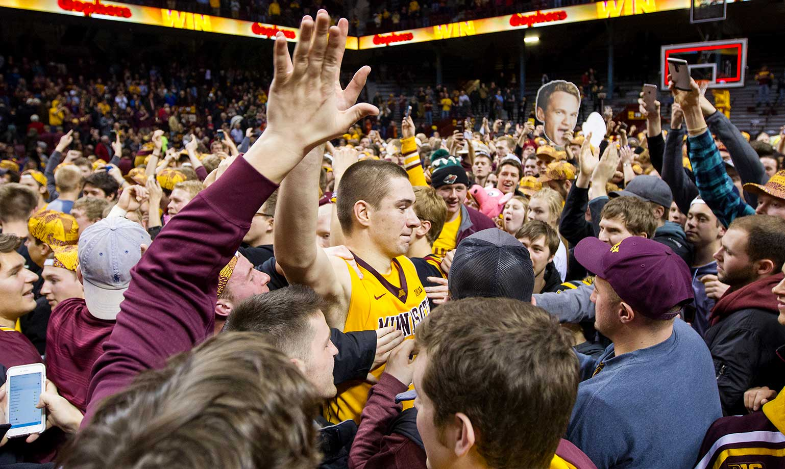 Joey King of the Minnesota Golden Gophers high fives a fan after the Gophers upset No. 6 Maryland 68-63.