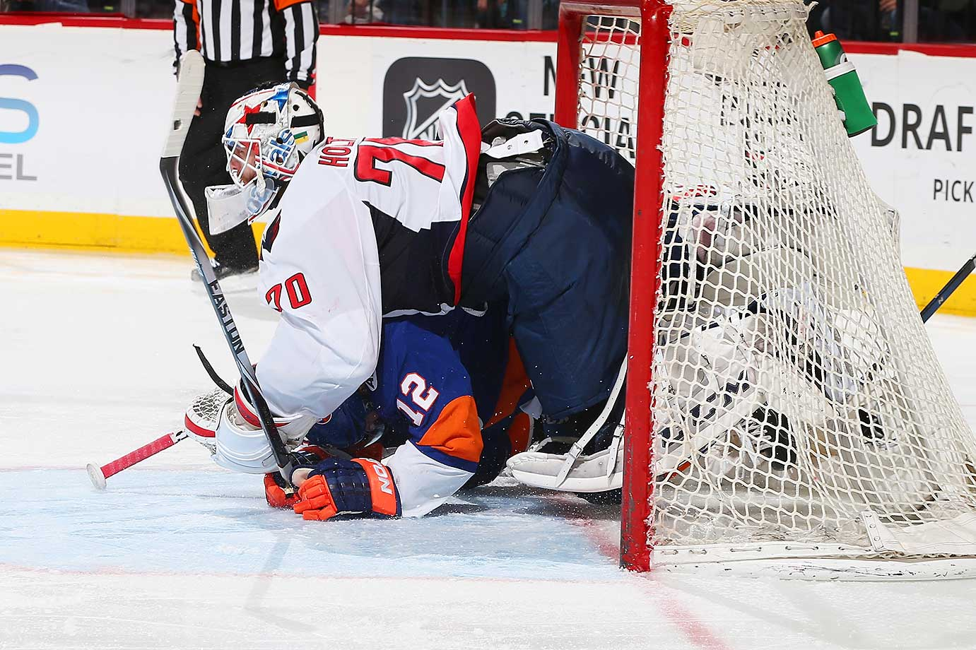 Josh Bailey of the New York Islanders collides with Braden Holtby of the Washington Capitals.