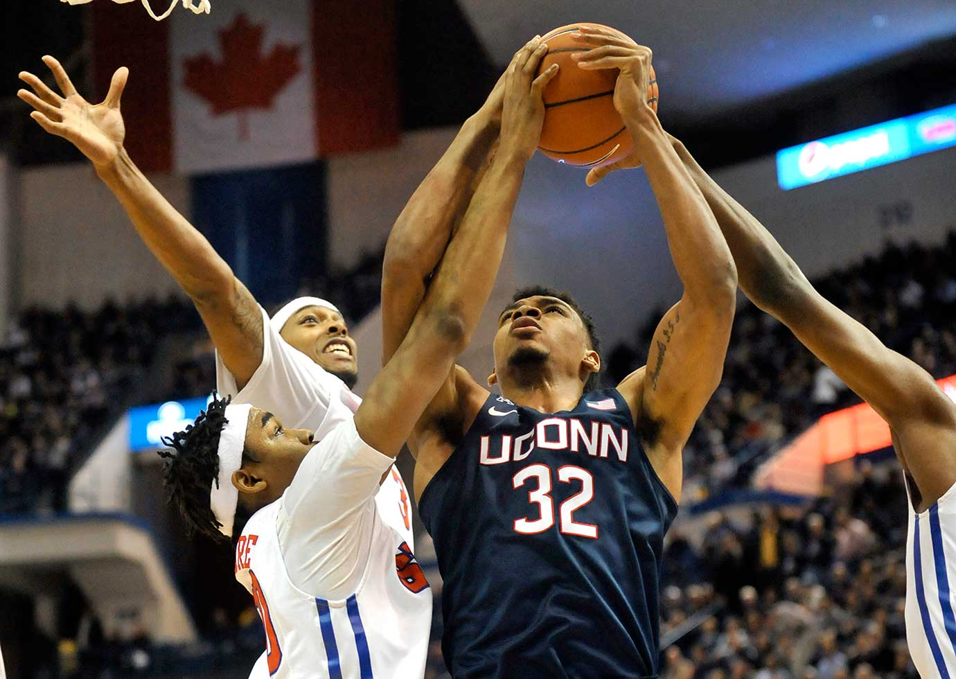 Connecticut's Shonn Miller takes the ball up against SMU's Sterling Brown, top, and Ben Moore (00).