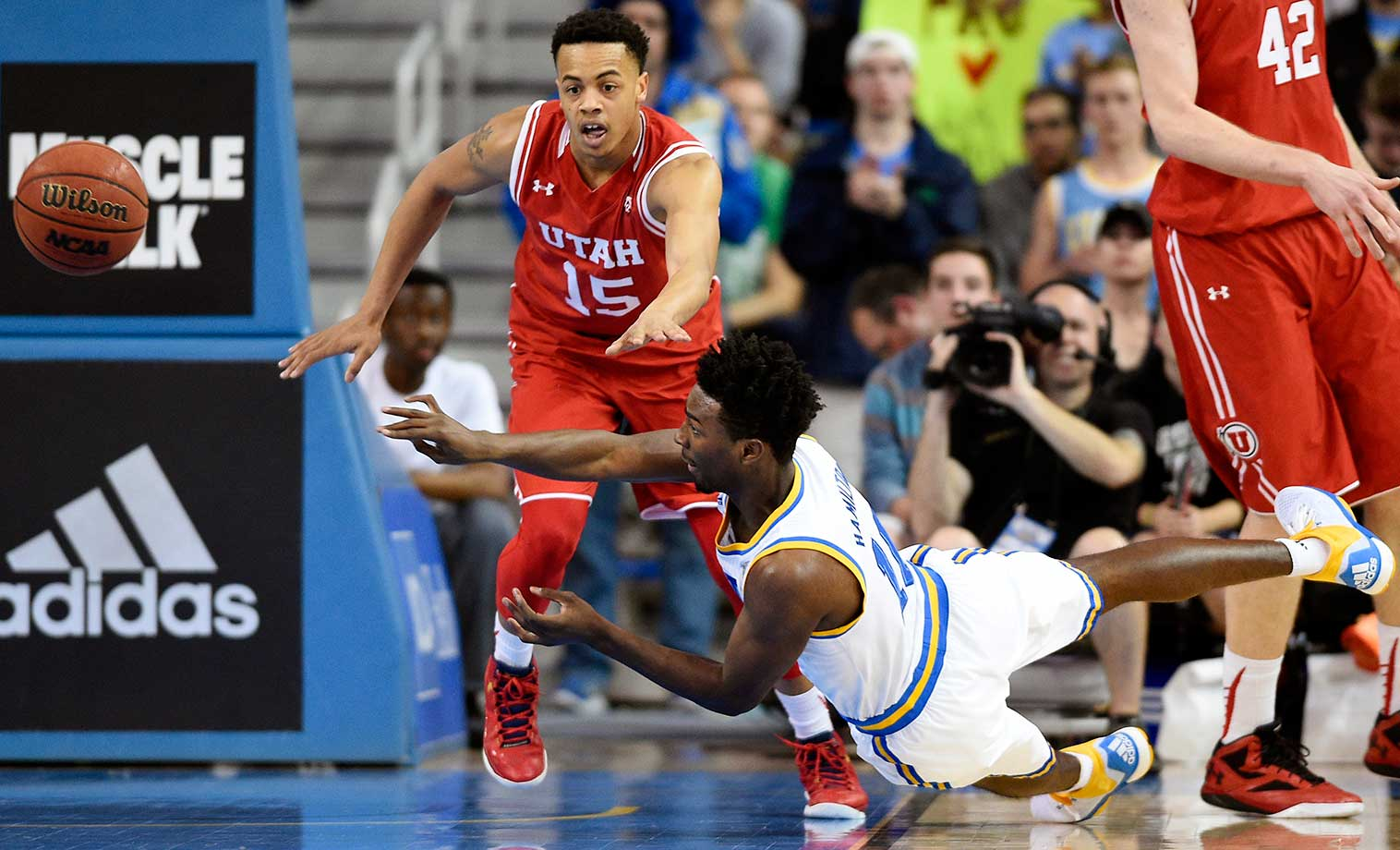 UCLA guard Isaac Hamilton passes the ball as he falls in front of Utah guard Lorenzo Bonam.