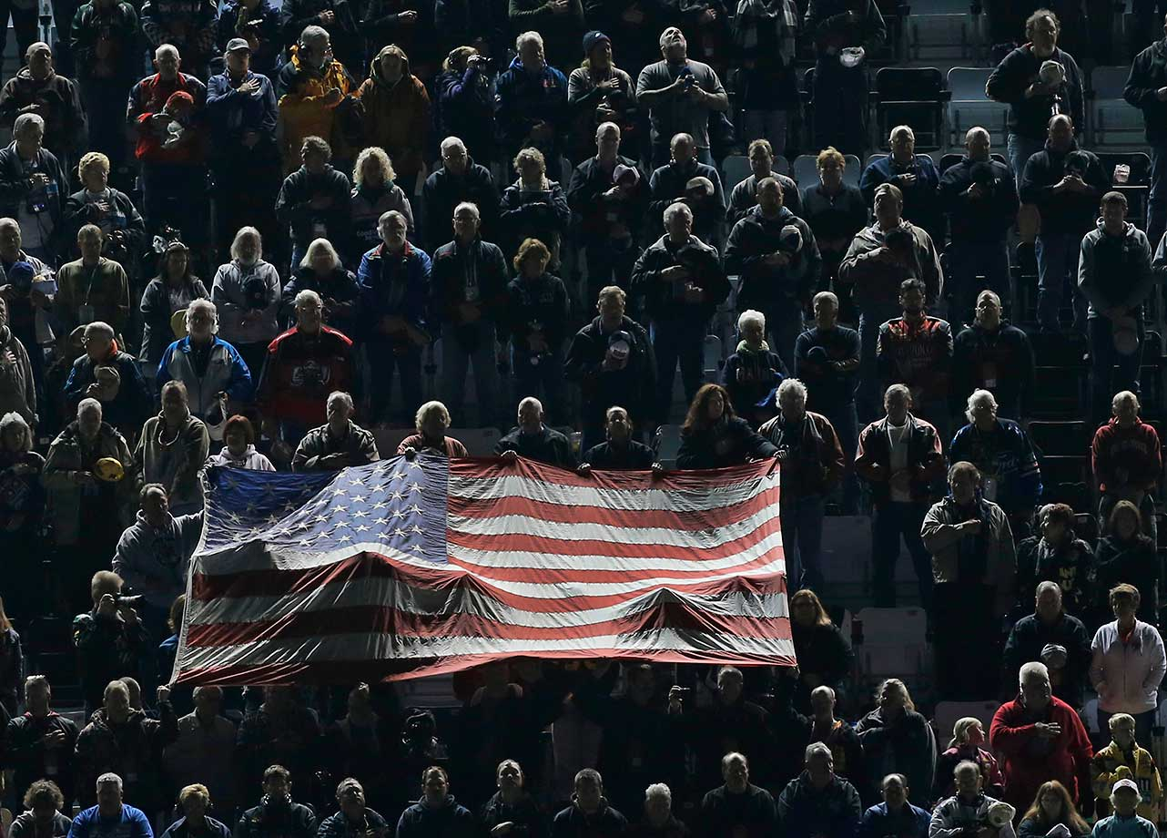 Race fans hold up a large U.S. flag during the singing of the national anthem before the first of two qualifying races for Sunday's Daytona 500.