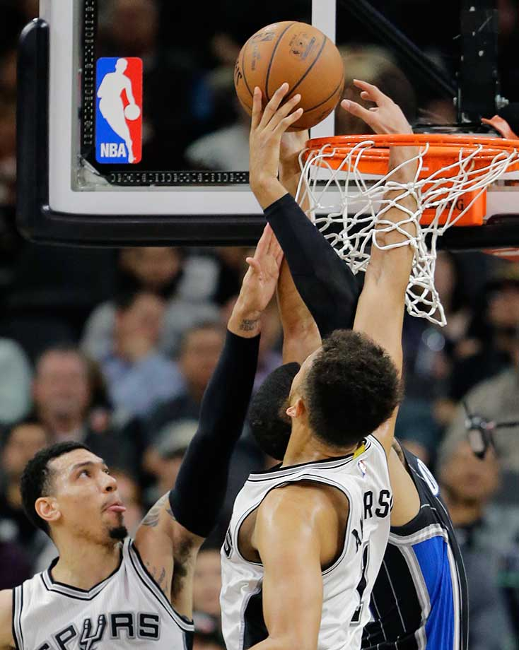 Kyle Anderson of the Spurs has his hand through the rim in an attempt to stop Orlando Magic forward Tobias Harris from scoring while teammate Danny Green helps out in San Antonio. The Spurs won 107-92.