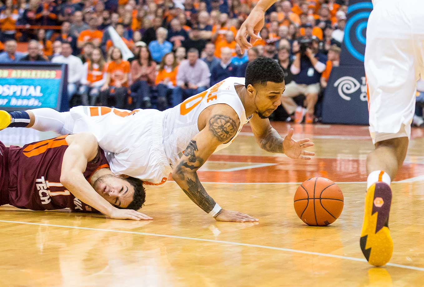 Michael Gbinije of the Syracuse Orange lands on Devin Wilson of the Virginia Tech Hokies as he dives for a loose ball at the Carrier Dome in New York.