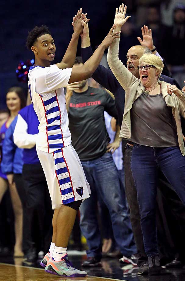 Eli Cain of the DePaul Blue Demons celebrates with fans after a 77-70 upset win over the Providence Friars at Allstate Arena in Rosemont, Ill.