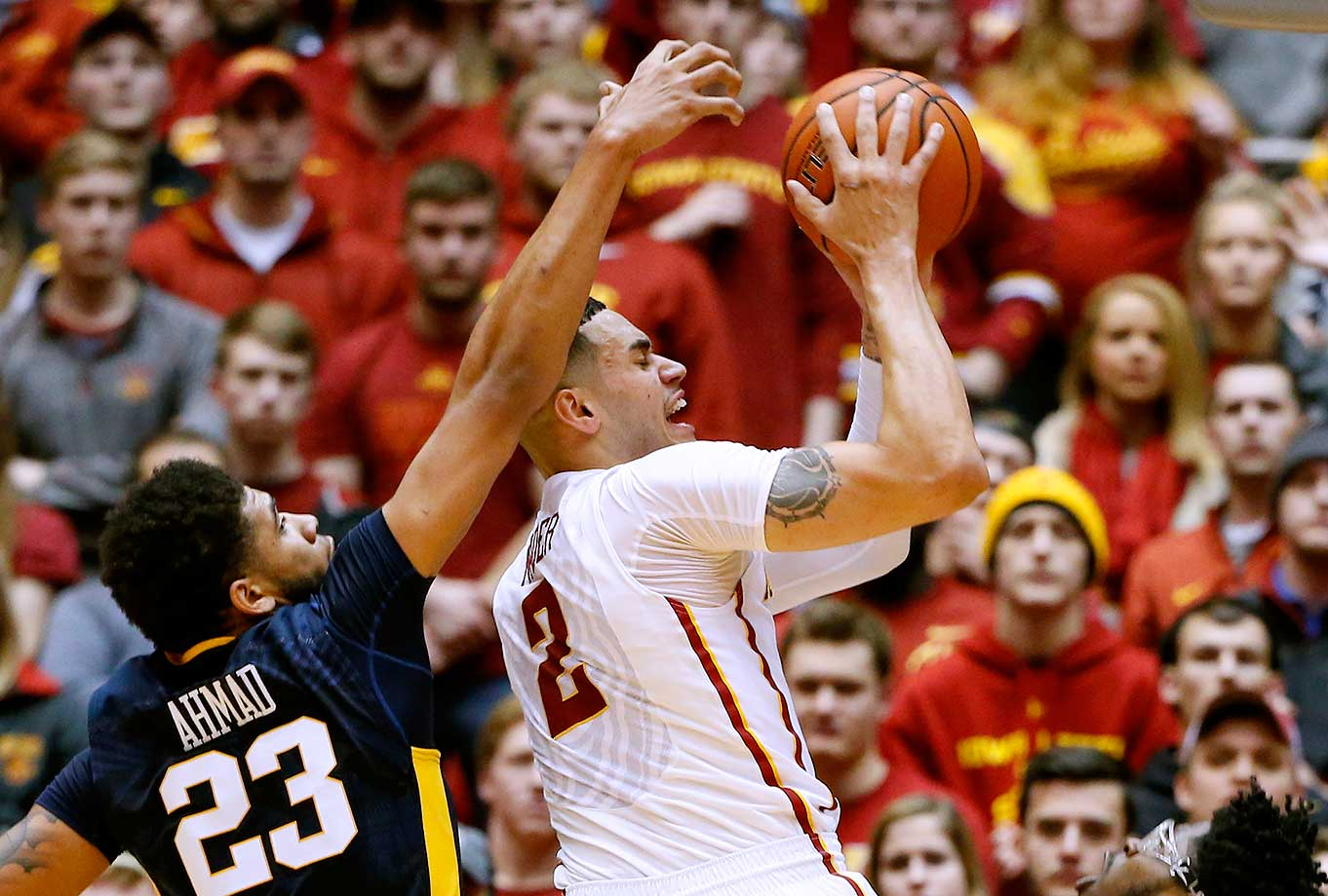 Abdel Nader of the Iowa State Cyclones is fouled by Esa Ahmad of the West Virginia Mountaineers at Hilton Coliseum in Ames, Iowa. West Virginia won 81-76.