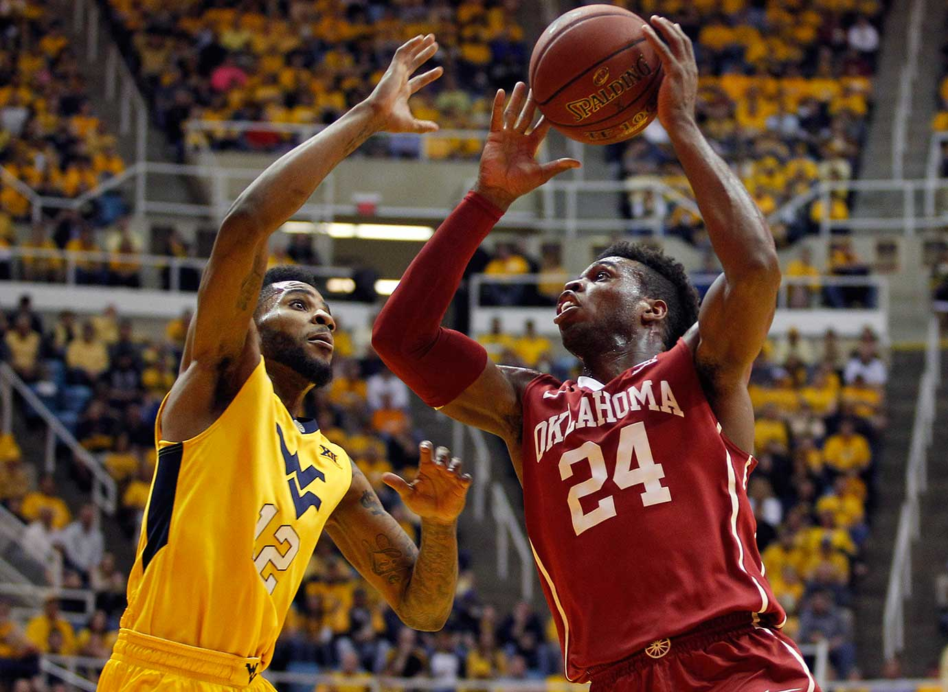 Buddy Hield of the Oklahoma Sooners shoots against Tarik Phillip of the West Virginia Mountaineers.