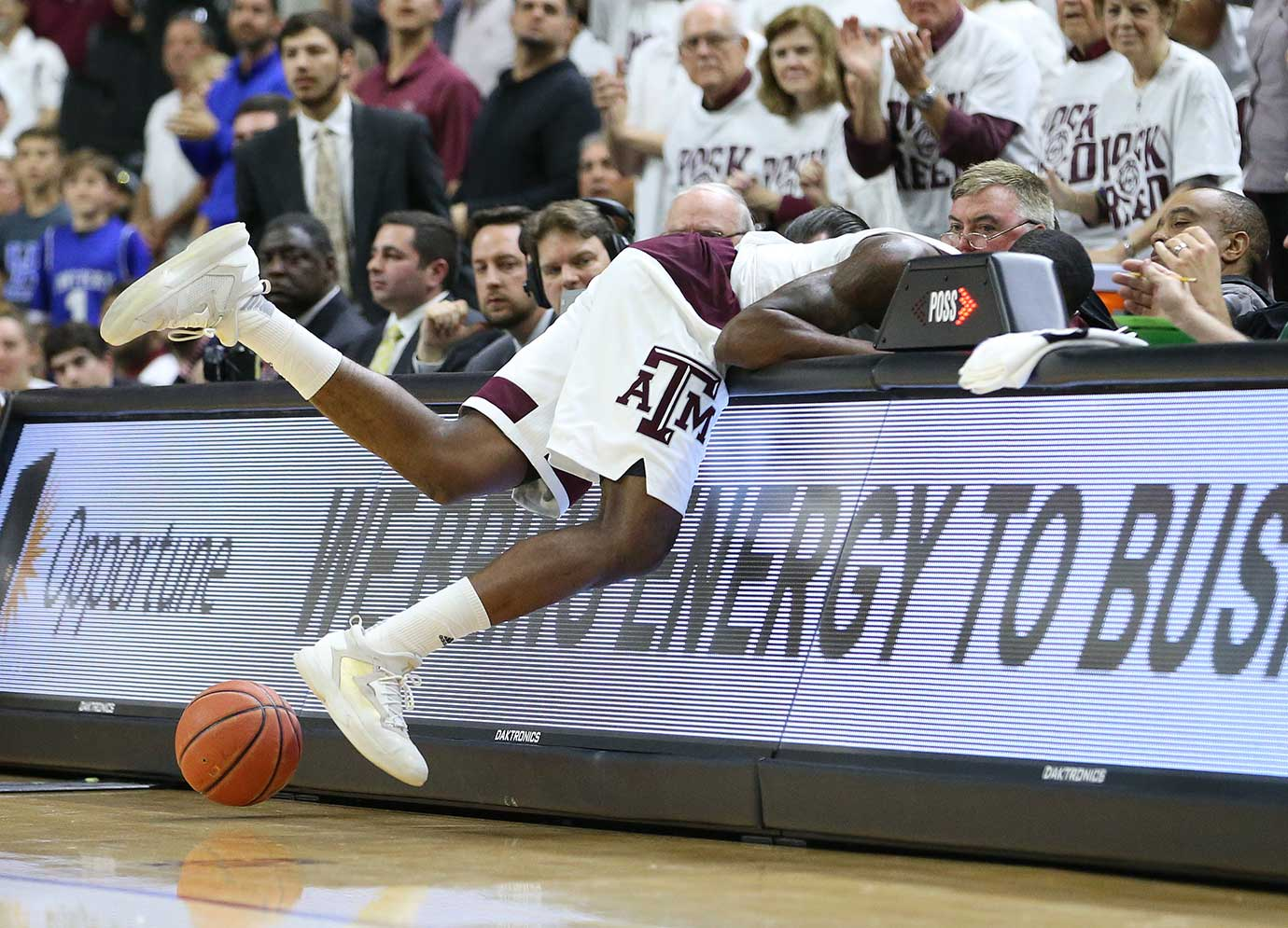 Texas A&M's Jalen Jones dives into the scorer's table while chasing a loose ball against Kentucky.