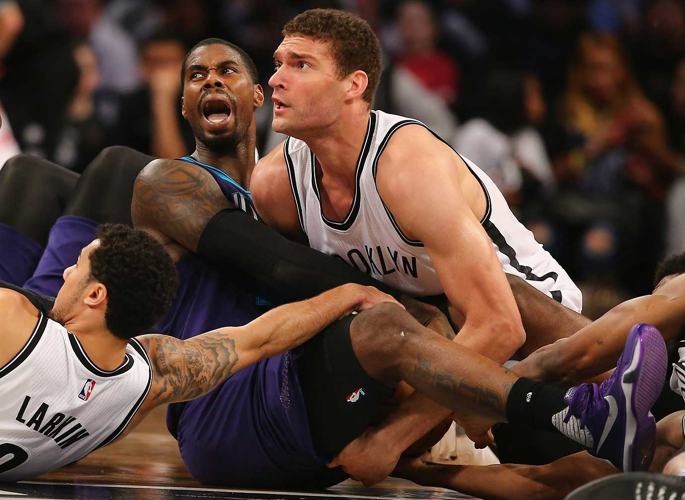 Marvin Williams of Charlotte and Brook Lopez of Brooklyn look to the ref for a ruling while battling for the ball.