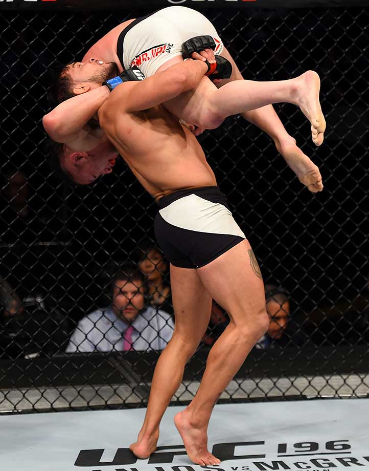 Dennis Bermudez takes down Tatsuya Kawajiri in their featherweight bout at the UFC Fight Night event in Pittsburgh.
