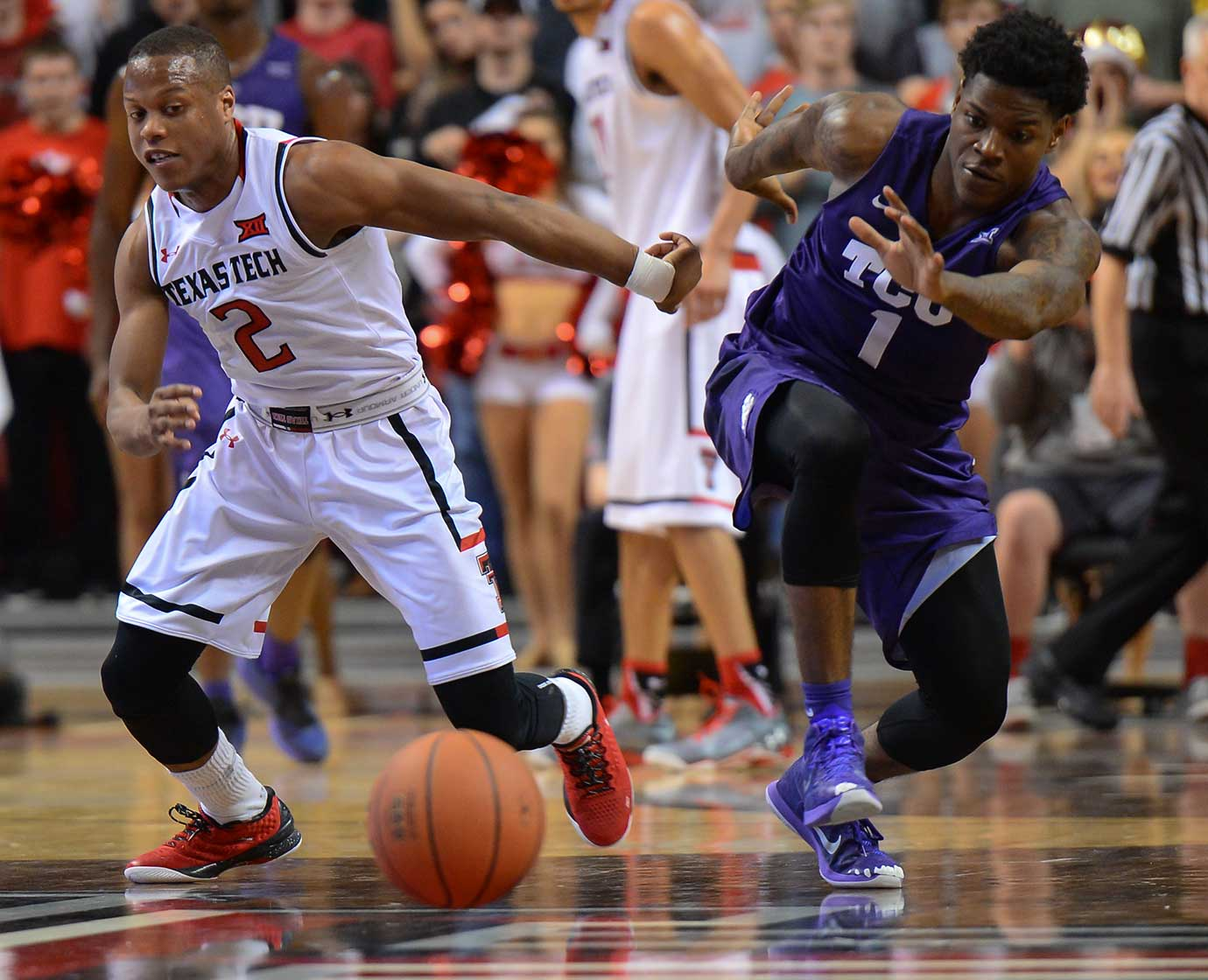 Devon Thomas of Texas Tech and Chauncey Collins of TCU try to regain their footing to get to a loose ball first.
