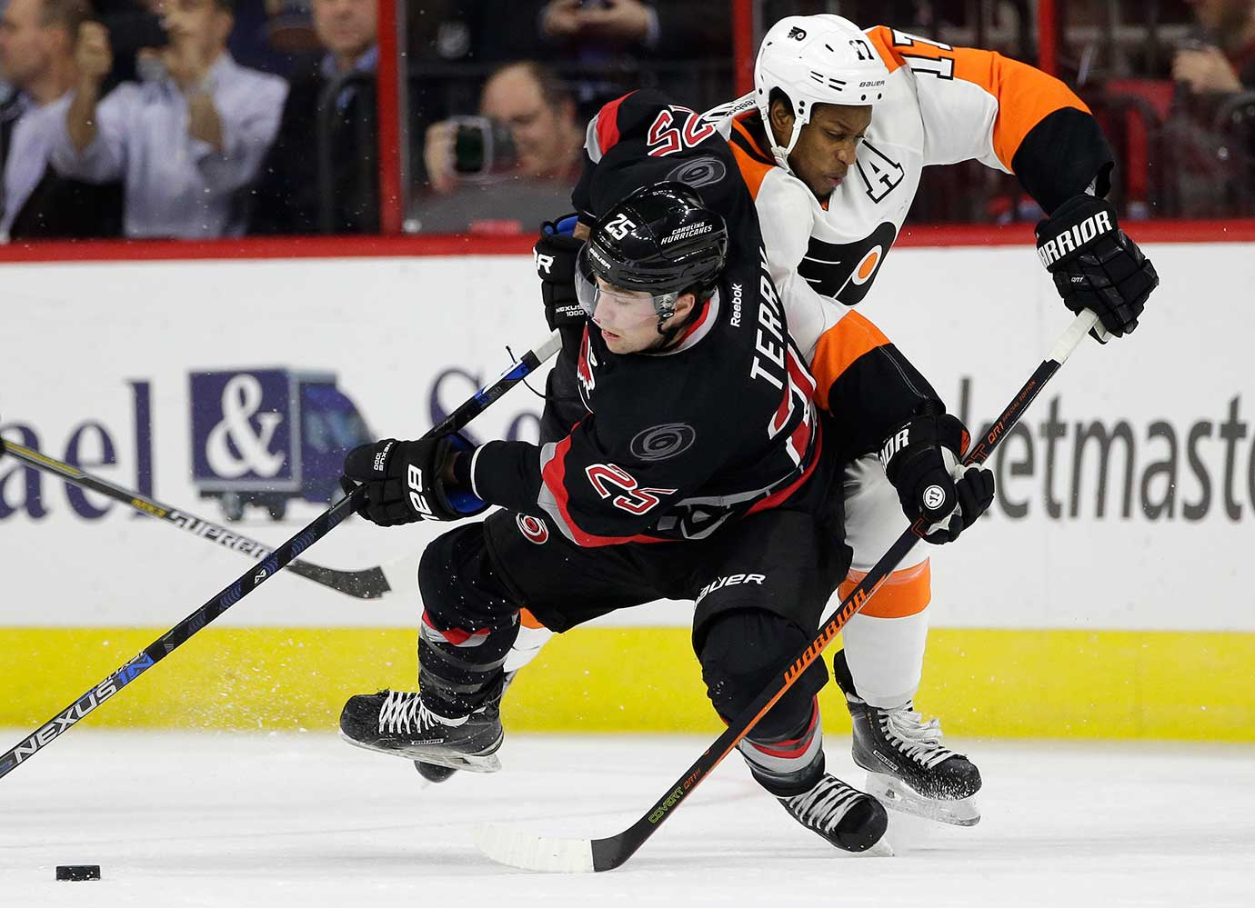 Chris Terry of Carolina, left, and Wayne Simmonds of Philadelphia chase the puck.