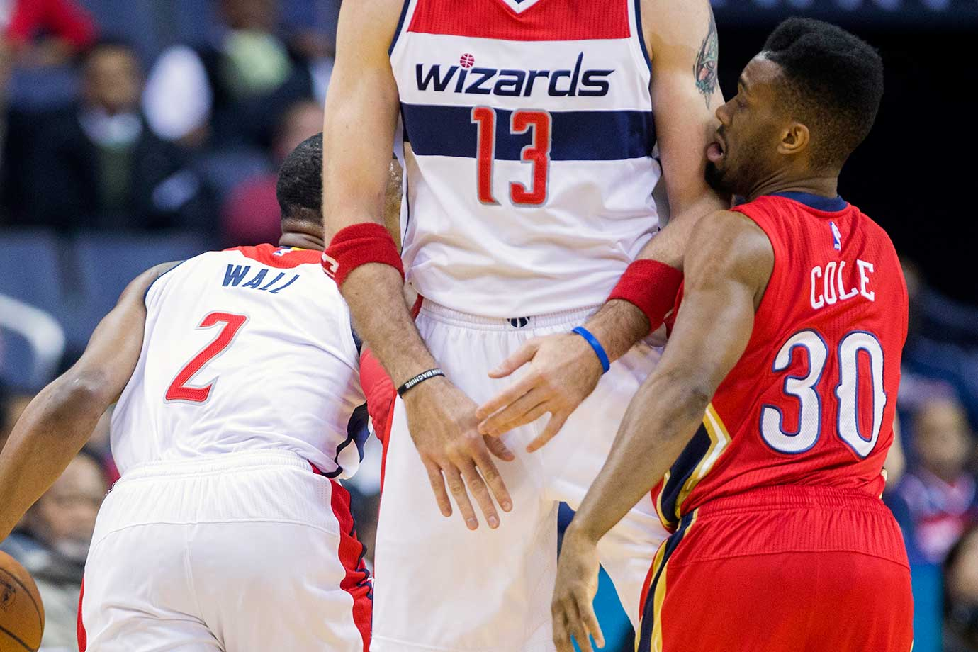 "New Orleans guard Norris Cole (6'2"") gets caught in a pick set by 6'11"" Washington center Marcin Gortat."