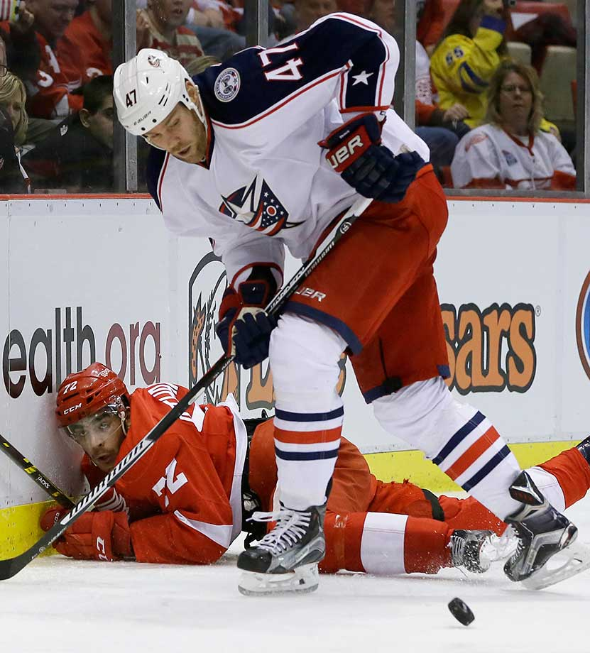 Columbus defenseman Dalton Prout chases the puck after checking Detroit's Andreas Athanasiou.