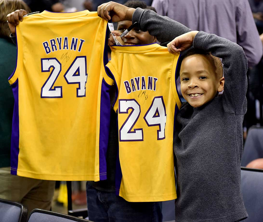 Young fans hold up jerseys autographed by Kobe Bryant prior to a game at Memphis.